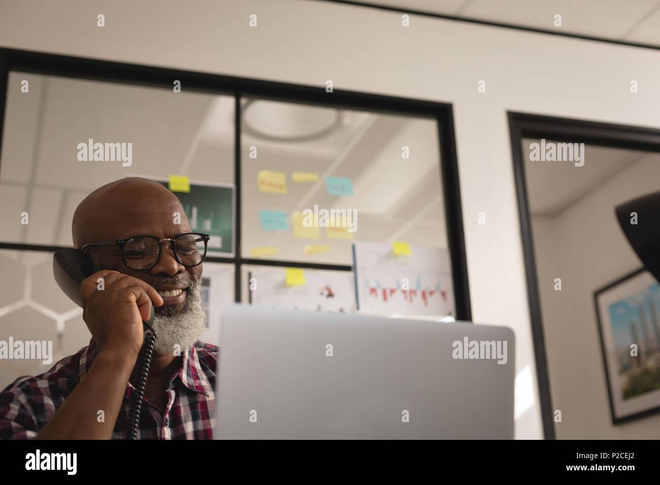 Senior graphic designer talking on landline phone - Stock Image