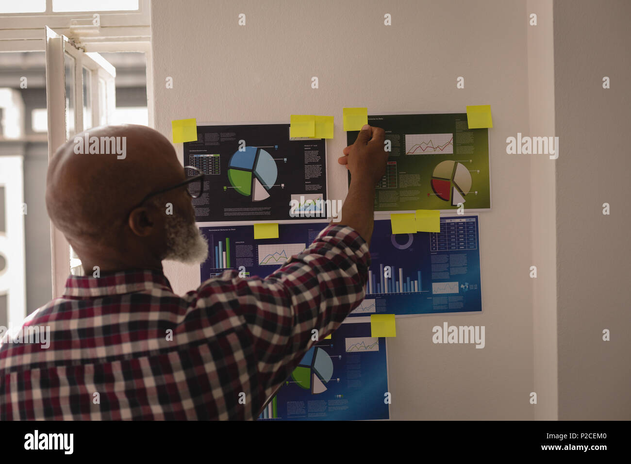 Senior graphic designer looking at sticky notes - Stock Image