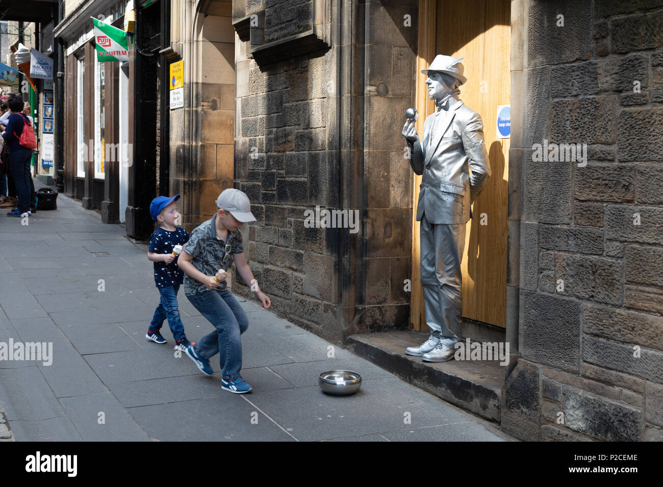 Children giving money to a street performer performing, the Royal Mile, Edinburgh old town, Scotland UK - Stock Image