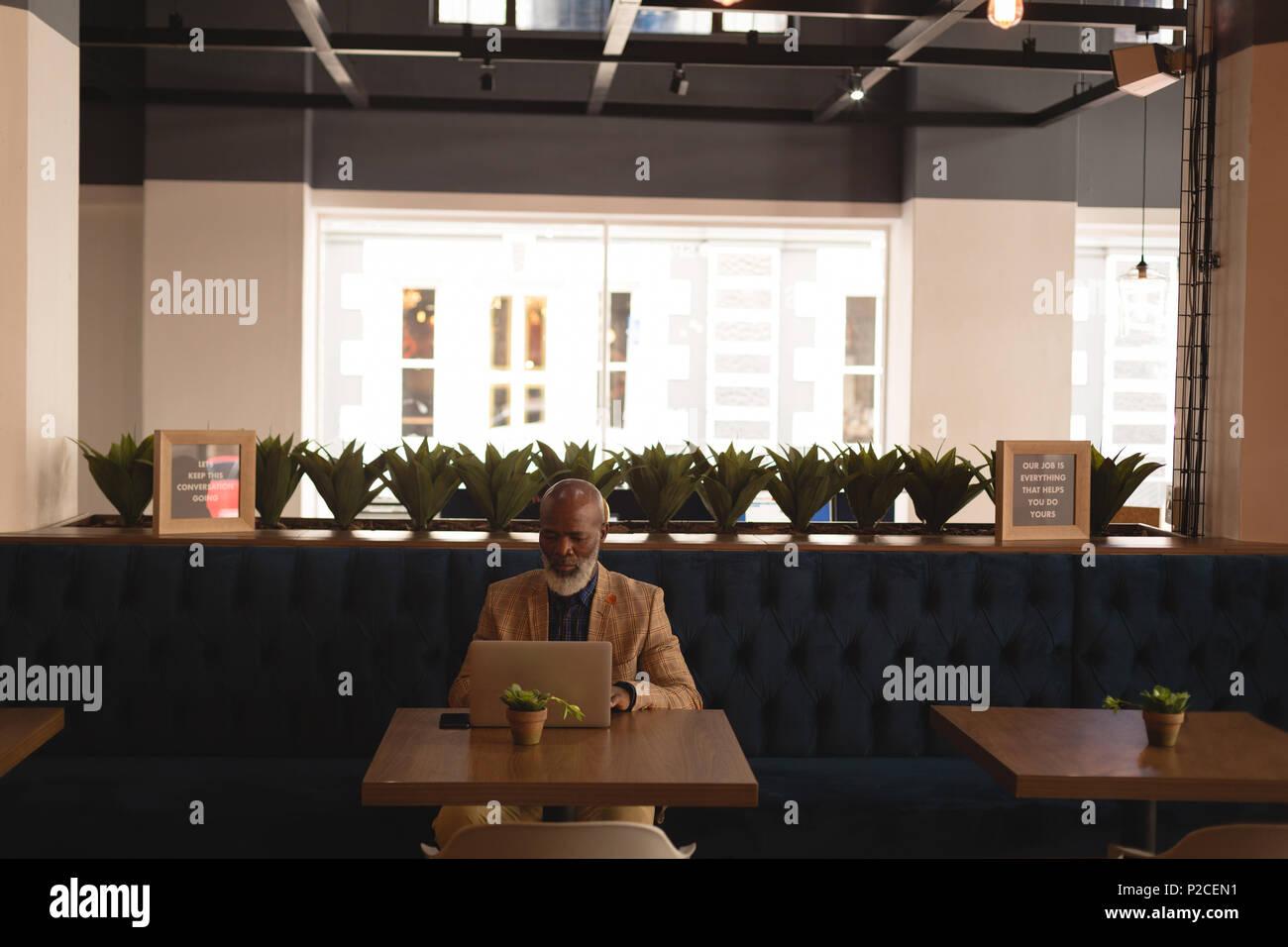 Senior graphic designer using laptop in cafeteria - Stock Image