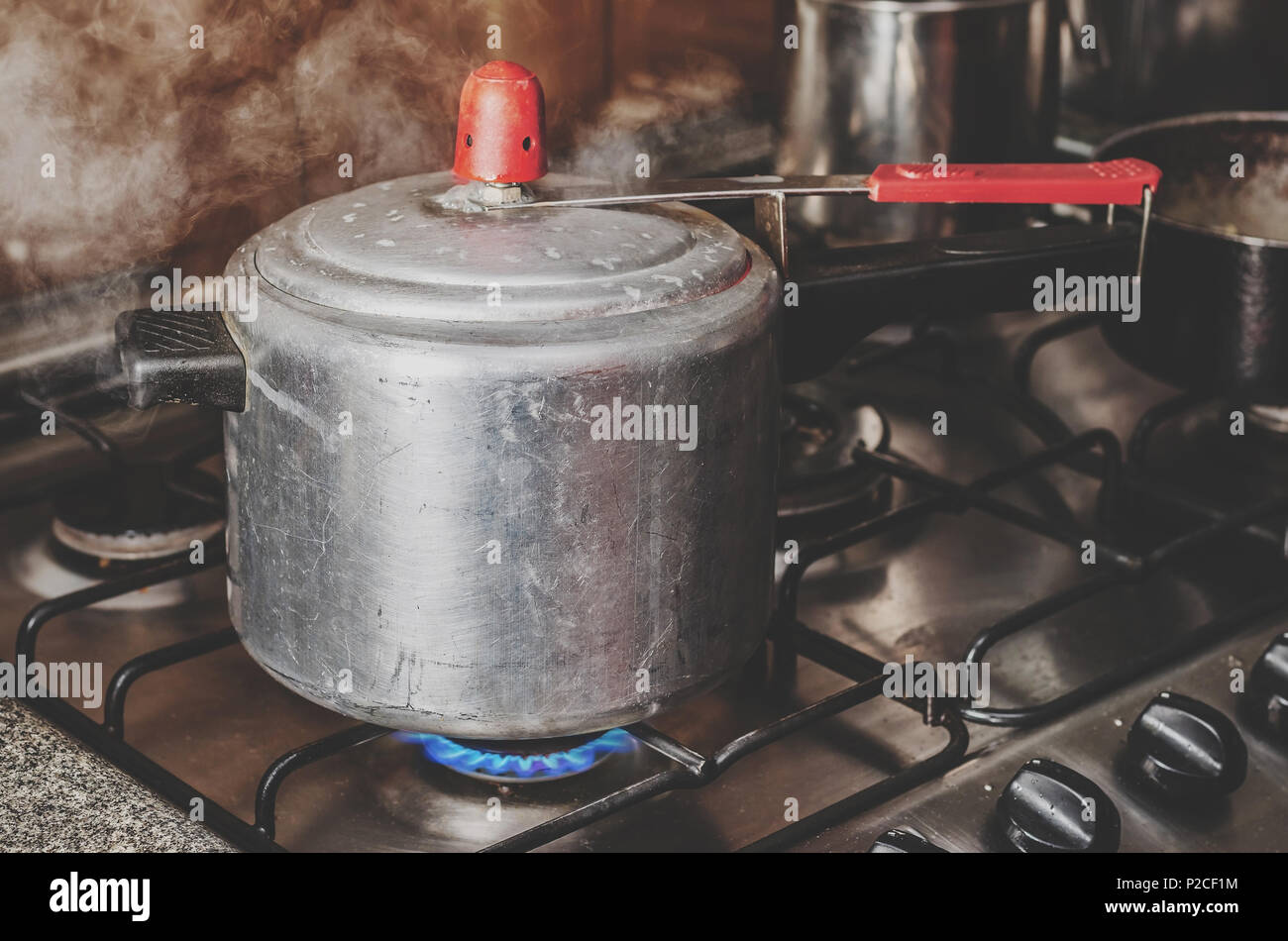 Cooking beans on the pressure cooker. Hot pressure cooker pan with steam getting out. Pressure pan on the stove. - Stock Image