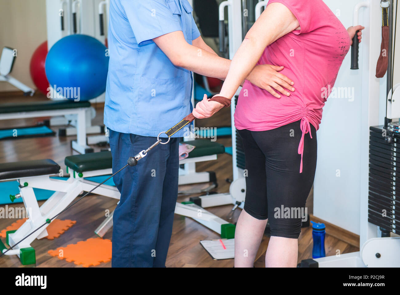 No face elderly woman doing active, special exercises guided by physical therapist at the hospital rehabilitation center. Osteopathy, chiropractic, ph - Stock Image