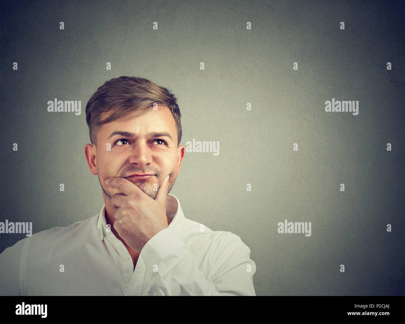 Handsome pensive man holding hand on chin and thinking thoroughly while looking up on gray - Stock Image