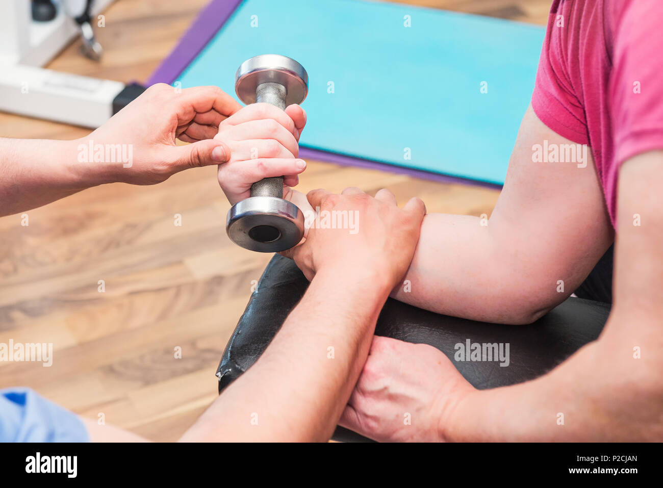 No face elderly woman doing active, working with dumbbell guided by physical therapist at the hospital rehabilitation center. Osteopathy, chiropractic - Stock Image