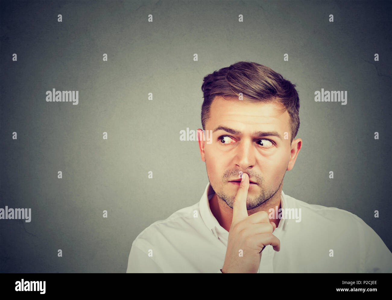 Man asking for silence and secrecy holding finger on lips and looking away in conspiracy - Stock Image