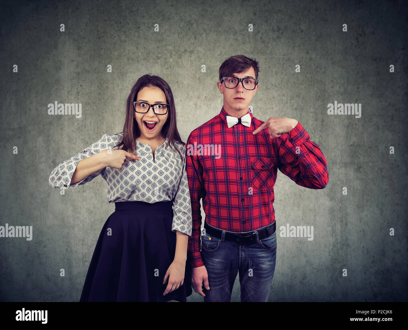 Young stunned man and woman standing together and pointing at themselves being selected - Stock Image