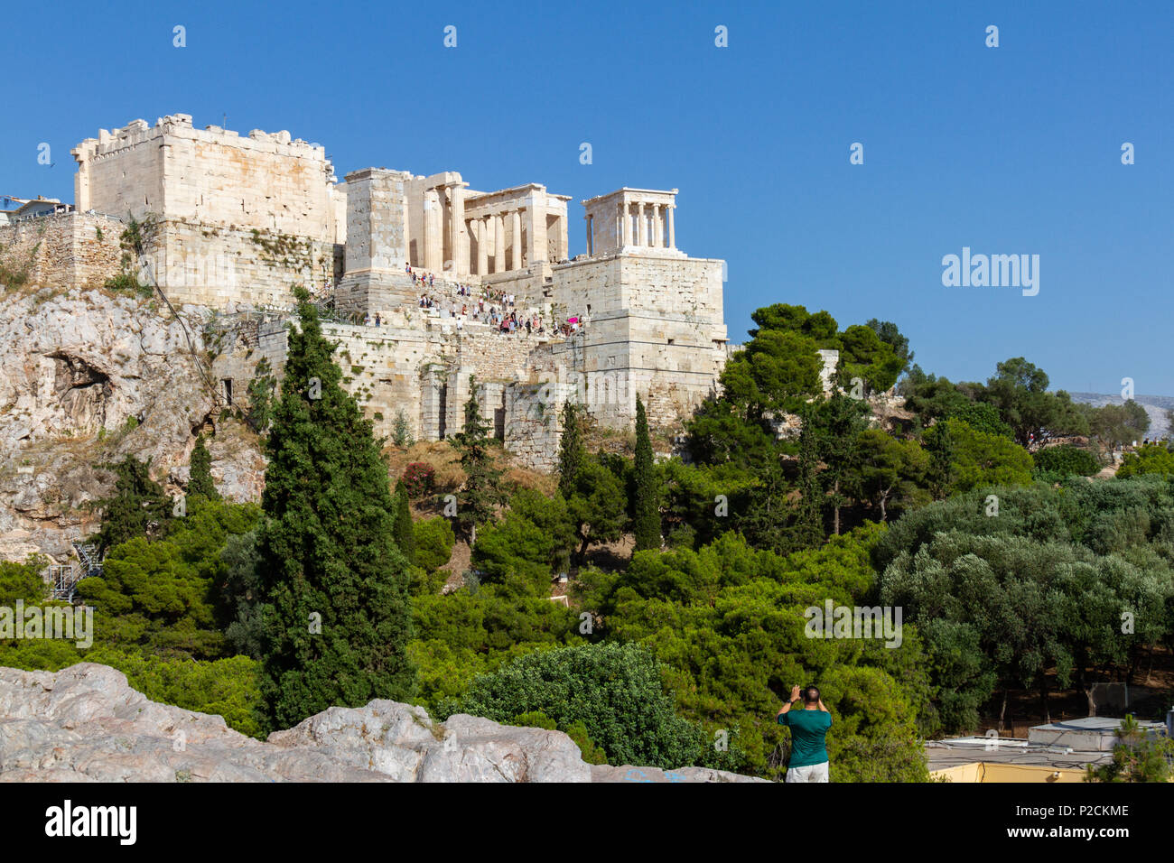 Tourist taking a photo of the Acropolis of Athens, Greece from a rocky hill across the Acropolis rock - Stock Image