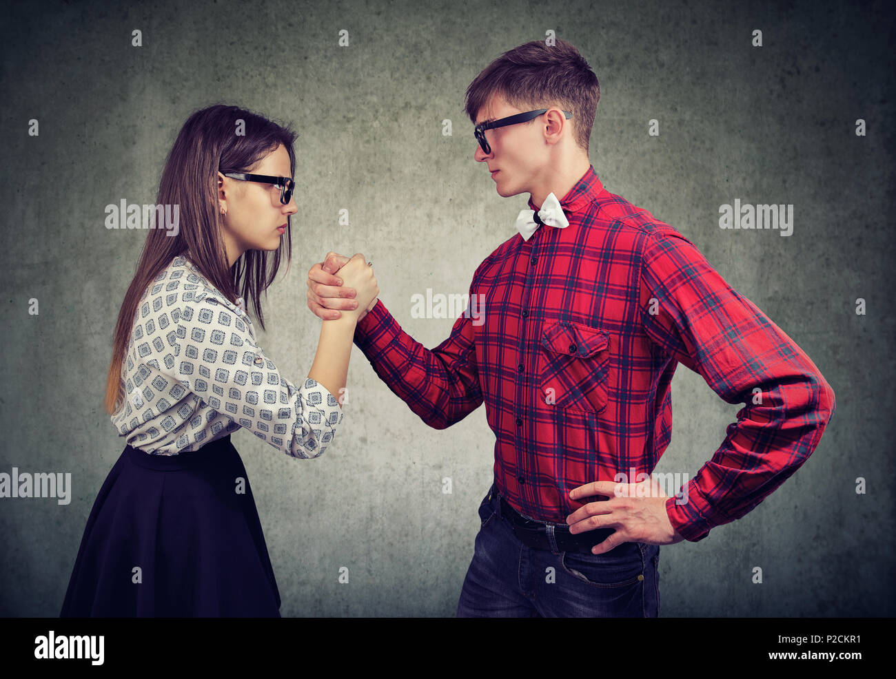 Young man and woman having competition in arm wrestling looking at each other in domination. - Stock Image