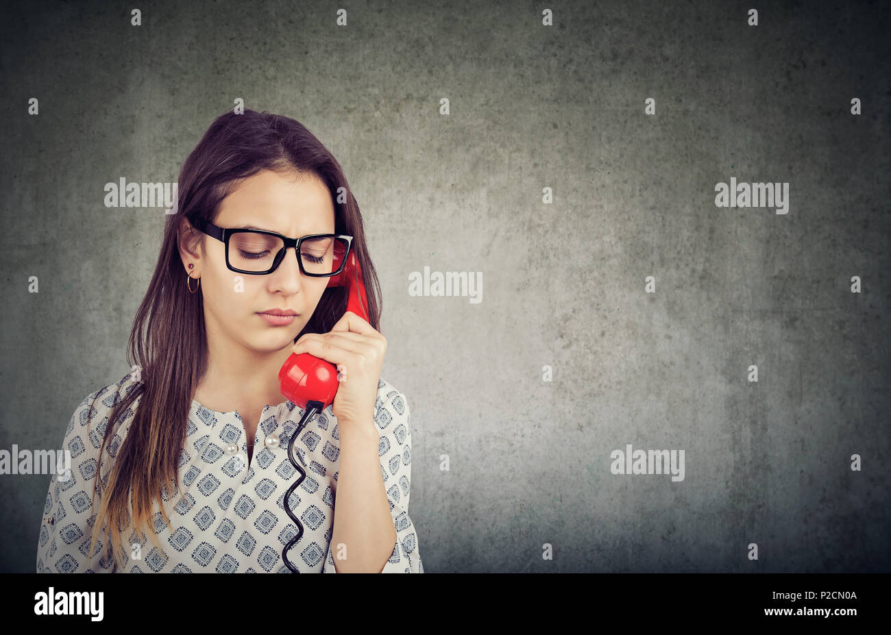 Pretty girl in glasses looking down in sadness while speaking on phone and having problems - Stock Image