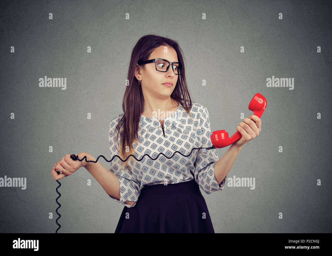 Confused young woman with bad news on the phone - Stock Image
