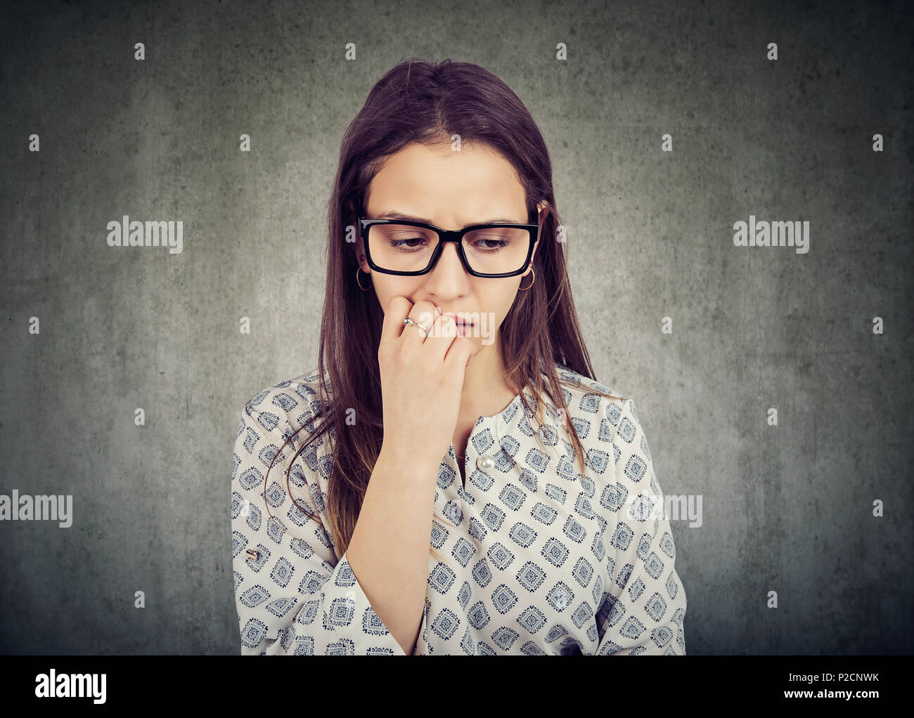 Nervous woman biting nails and looking down feeling insecure - Stock Image