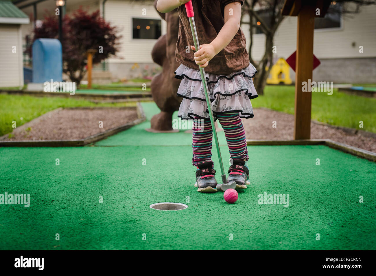 A young girl plays miniature golf in warmer weather. - Stock Image