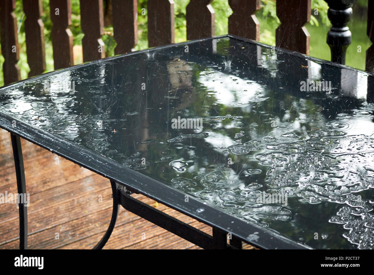 rain bouncing off a glass garden table during wet summer weather in the uk - Stock Image