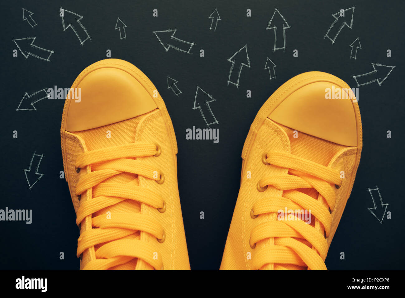 Making decisions and right choices conceptual image with yellow sneakers on the road with small arrow imprints pointing to various directions - Stock Image
