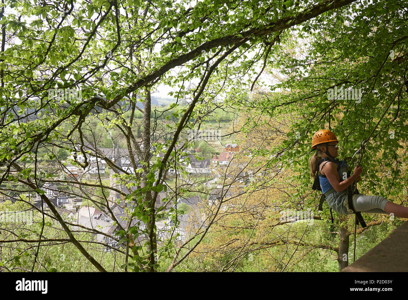 Young preteen girl trying out abseiling down a wall on a mountain with a village far away in the background Stock Photo