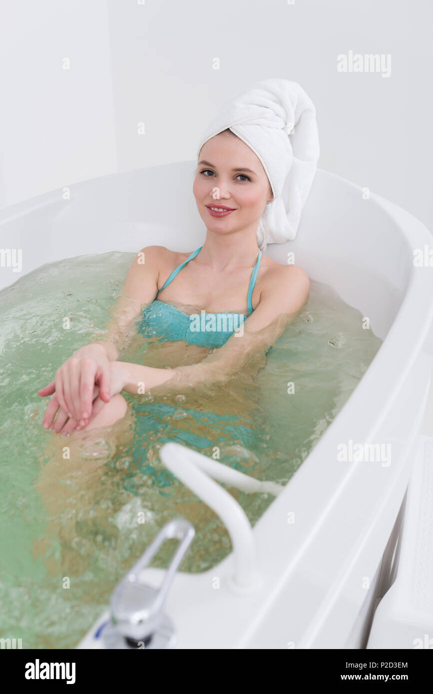 81e6de40fbae0 smiling woman in swimming suit with towel on head relaxing in bath in spa  salon -
