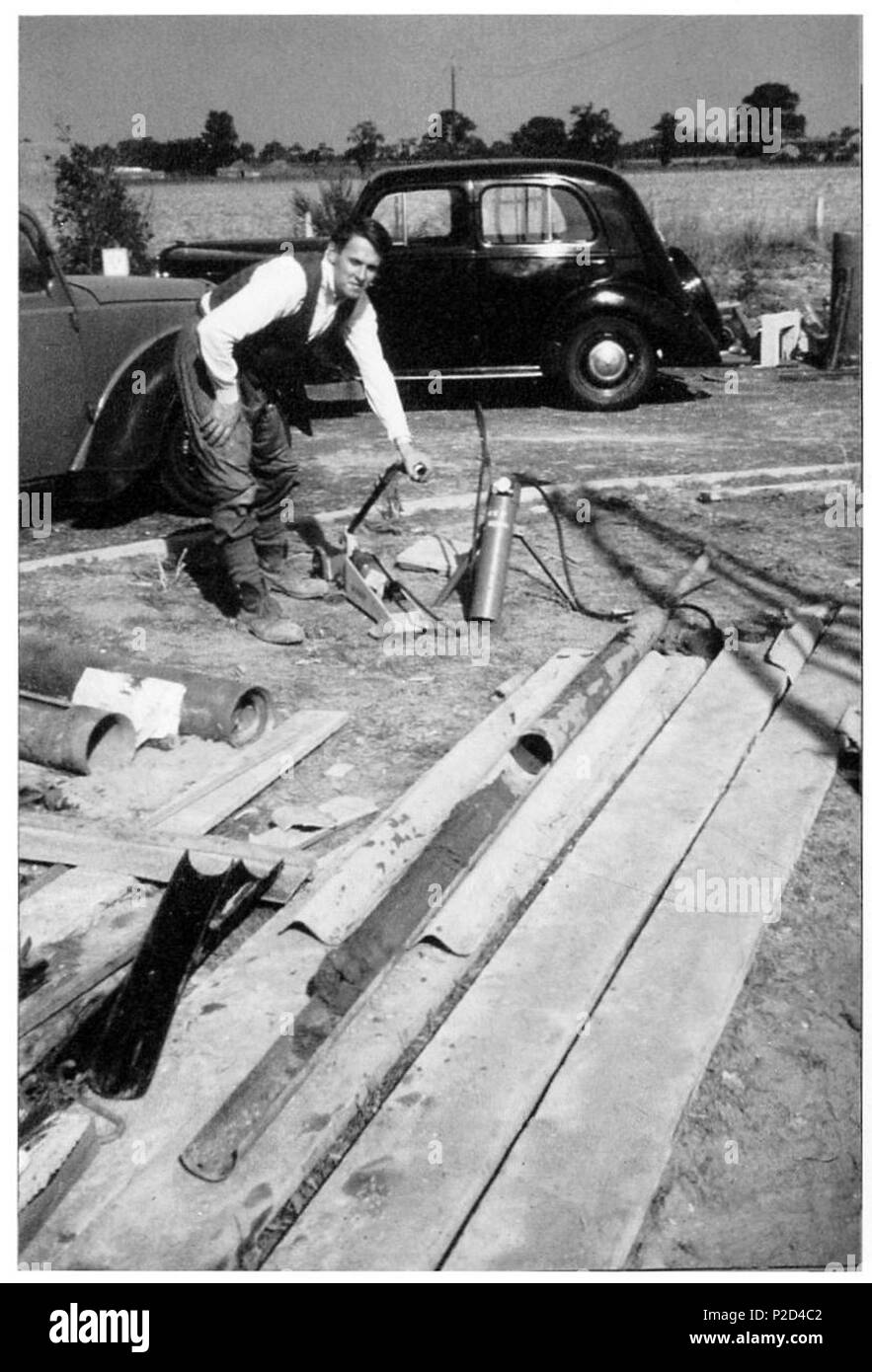 . English: Brian Funnell recovering core samples at the site of the Ludham Borehole, funded by the Royal Society of London, 1959. Image with kind permission Prof R.G. West. The Ludham Borehole was a geological research borehole drilled in 1959 near Ludham, Norfolk, UK. A continuous core sample of late Pliocene and early Pleistocene sediments of the Crag Group was recovered. Analysis allowed biostratigraphic zonal schemes for fossil pollen,foraminifera, mollusca and dinoflagellates to be constructed for horizons of the Red Crag Formation and Norwich Crag Formations, and for these formations to  - Stock Image