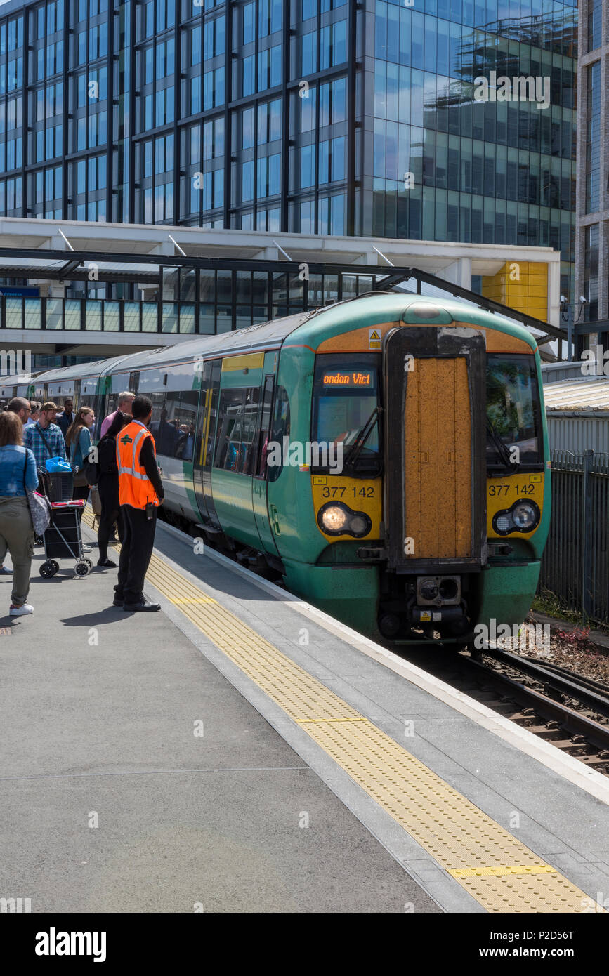 a southern railways service train in the platform at east croydon station in london with modern new contemporary developments in the background. Train - Stock Image