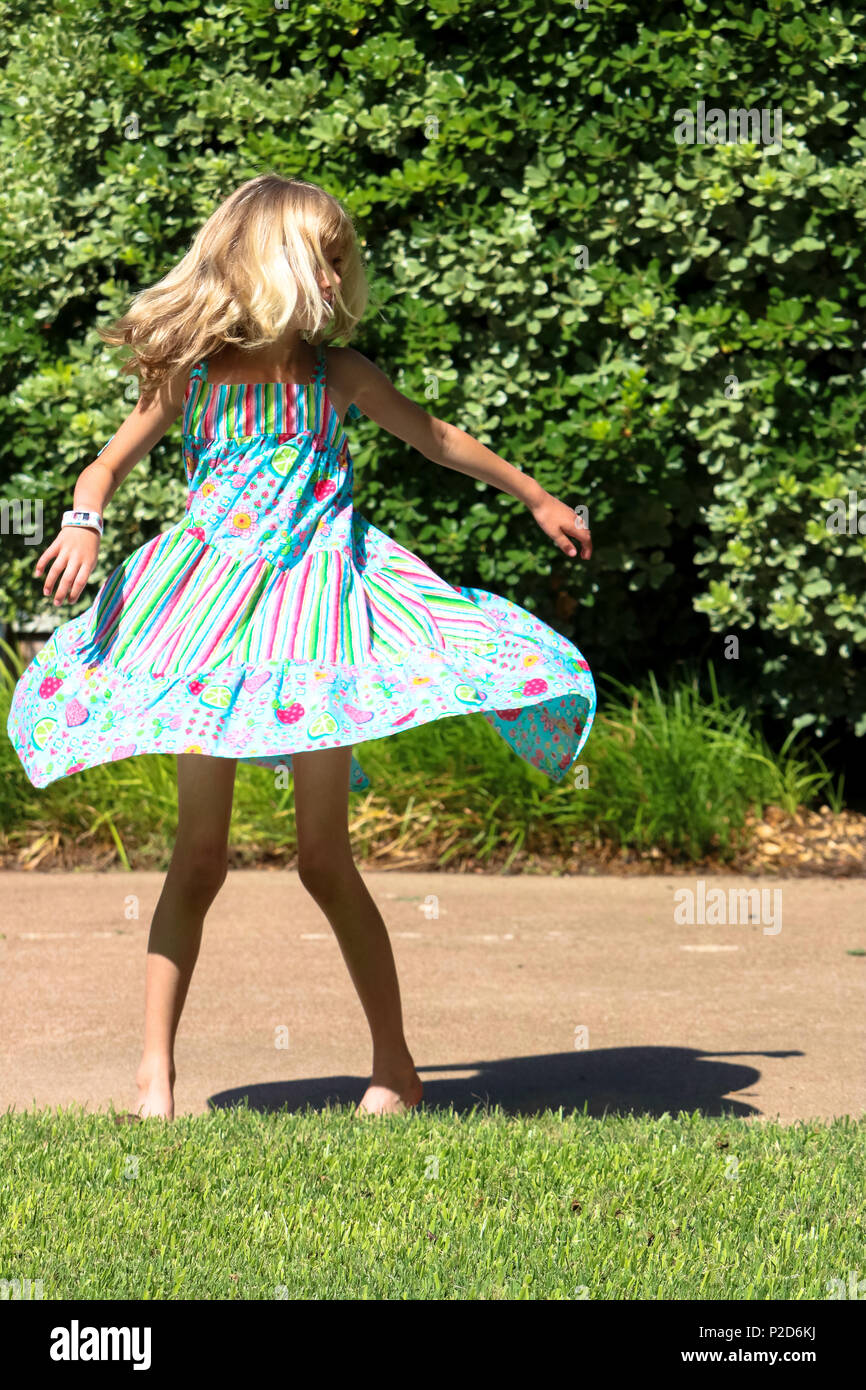 Young girl happily twirling in her summer dress - Stock Image