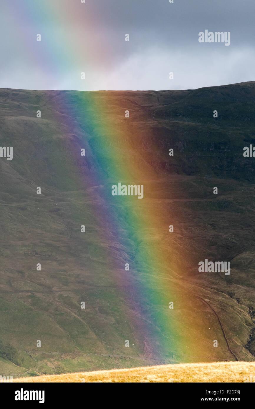 Rainbow over moorland after an autumn rain shower UK. - Stock Image