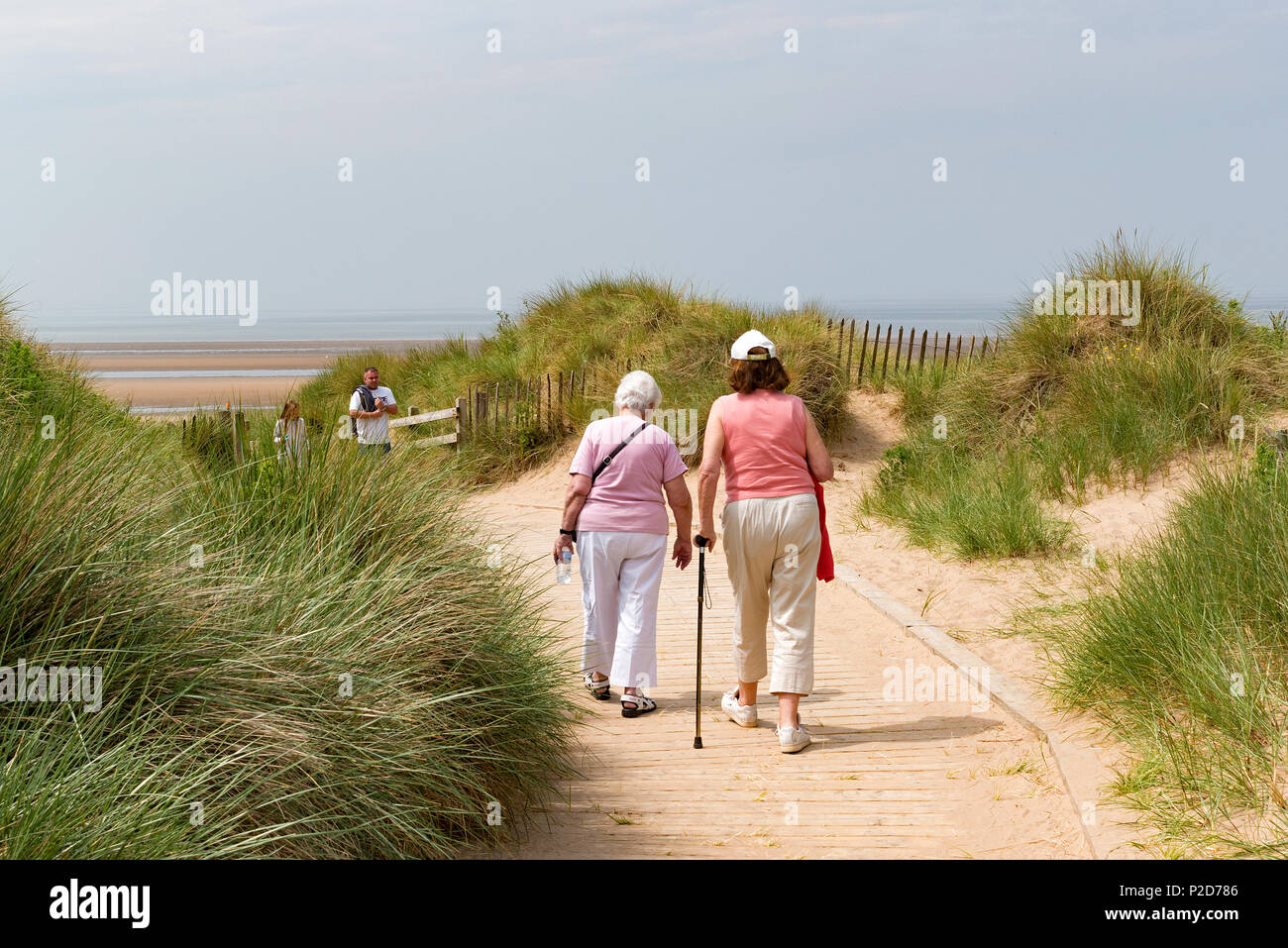 two senior ladies walking on a footpath at fomby beach near liverpool, england, britain, uk, - Stock Image