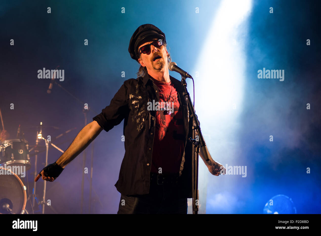 Rock lead singer on stage wearing a hat and sunglasses - Stock Image