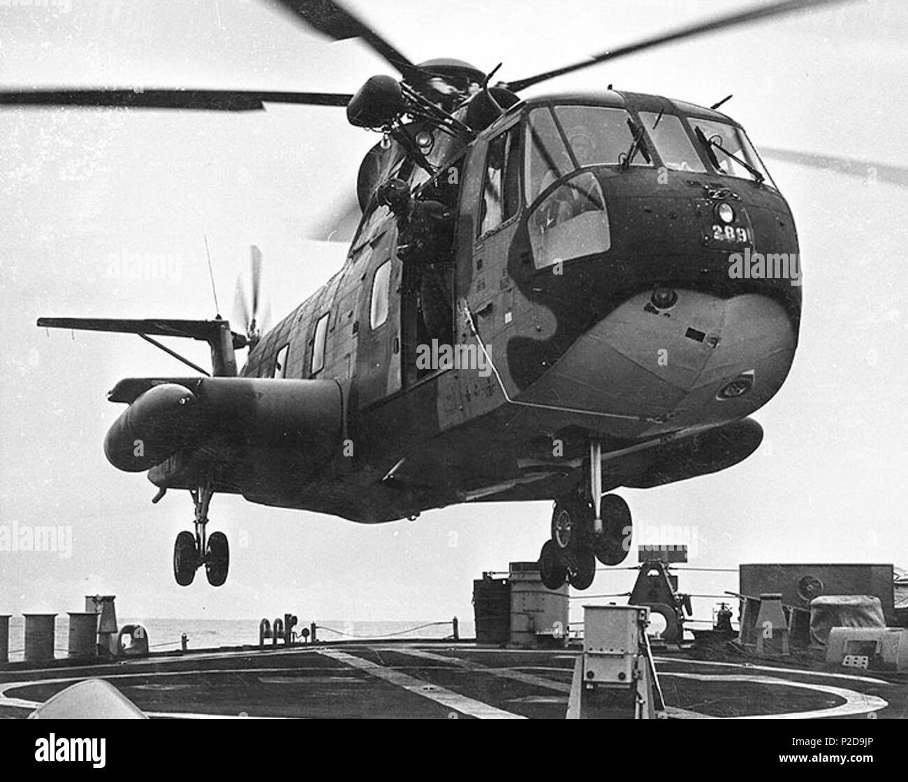 . A U.S. Air Force Sikorsky CH-3E Jolly Green Giant helicopter (s/n 66-13289) hovers over the after deck of the U.S. Navy guided missile destroyer USS William V. Pratt (DLG-13) on either 7 or 18 August 1967, while the ship was on Vietnam War duty in the Gulf of Tonkin. August 1967. USN 12 CH-3E hovers over USS William V. Pratt (DLG-13) off Vietnam in 1967 - Stock Image