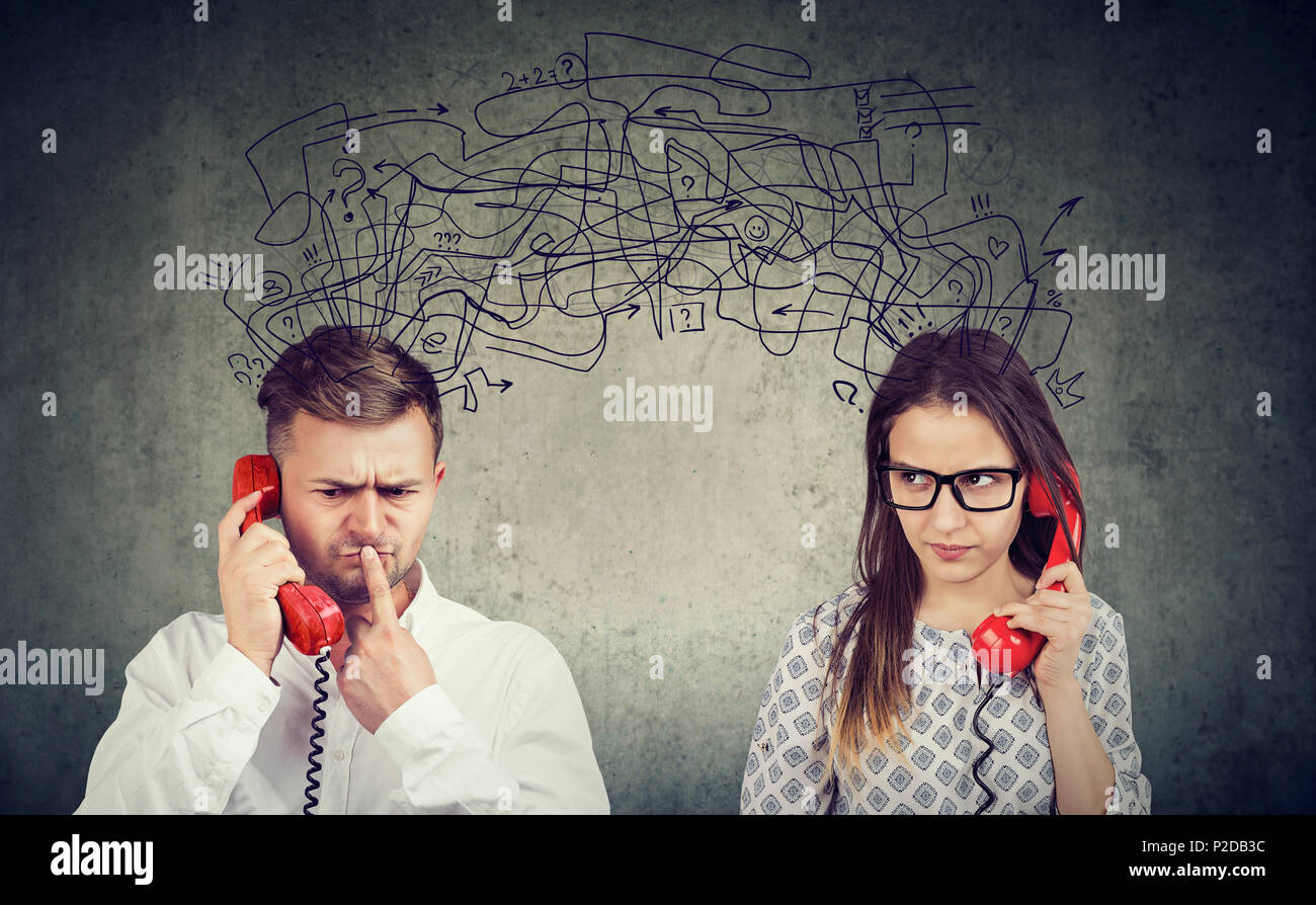 preoccupied confused couple woman and man talking on the phone exchanging with many negative thoughts - Stock Image