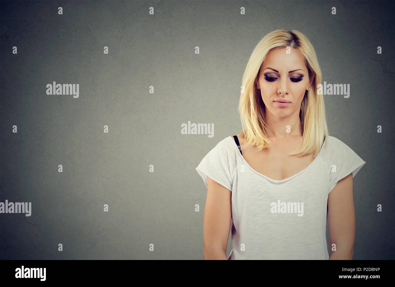 Sad blonde woman looking down feeling hopeless - Stock Image