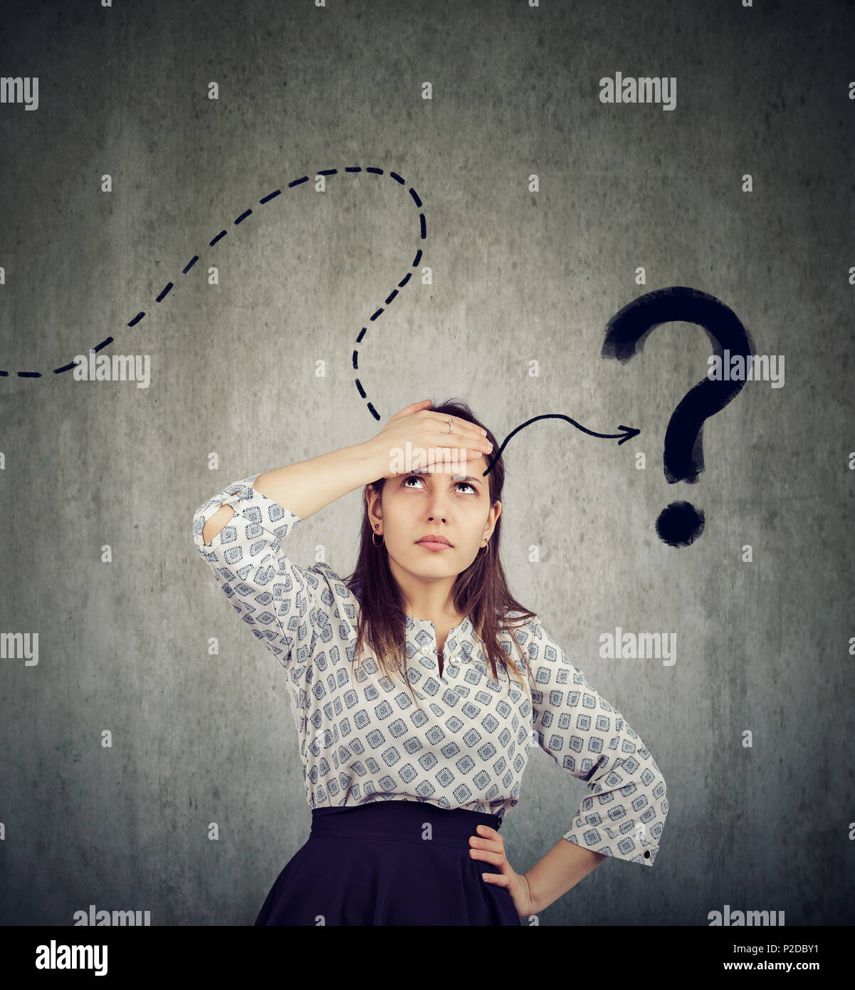Young woman thinking hard trying to remember has a question - Stock Image