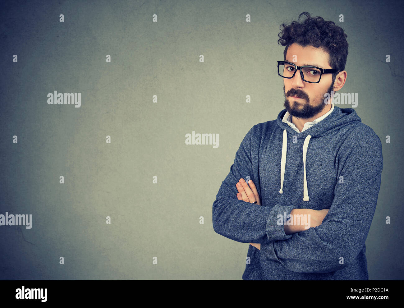 Casual hipster man in glasses holding hands crossed and looking at camera in hate being angry - Stock Image