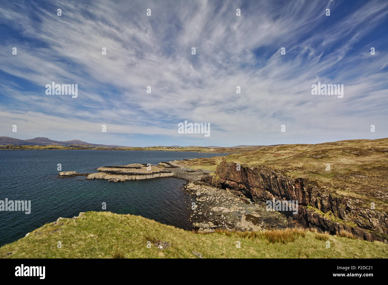 Sea cliff with low headland in the background and blue sky with white cirrus clouds Stock Photo