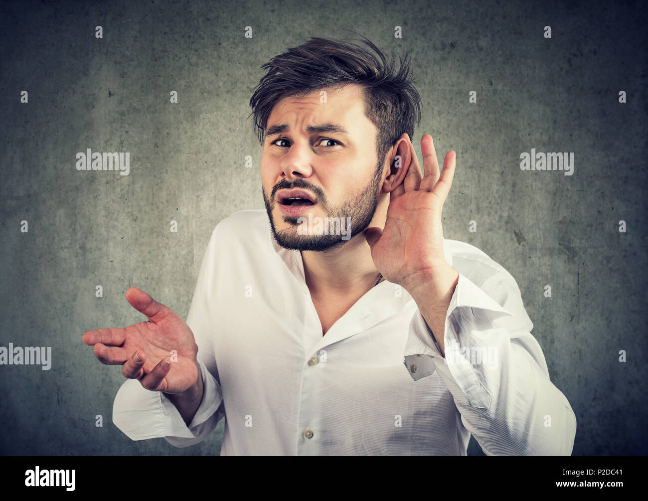 Frowning young man having problems with hearing and looking at camera in misunderstanding gesturing to speak louder - Stock Image