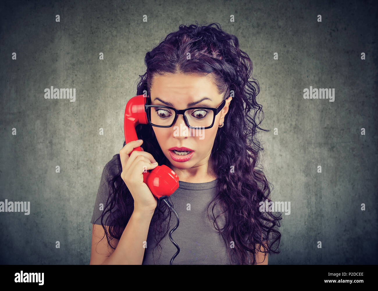 Young brunette in glasses receiving bad news and looking stunned while speaking on phone - Stock Image