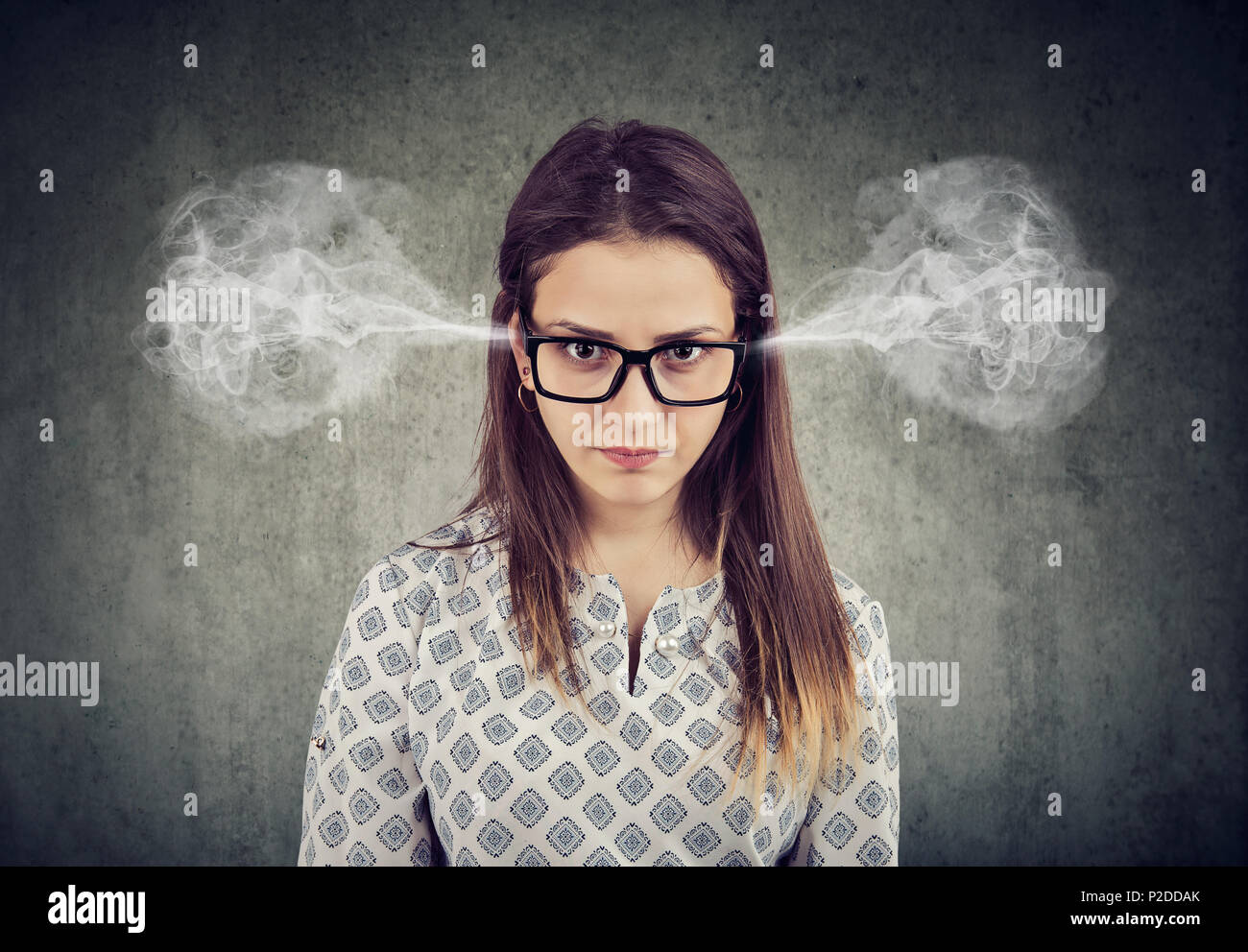 Closeup portrait of angry woman, blowing steam coming out of ears isolated on gray background. Negative human emotions feelings - Stock Image