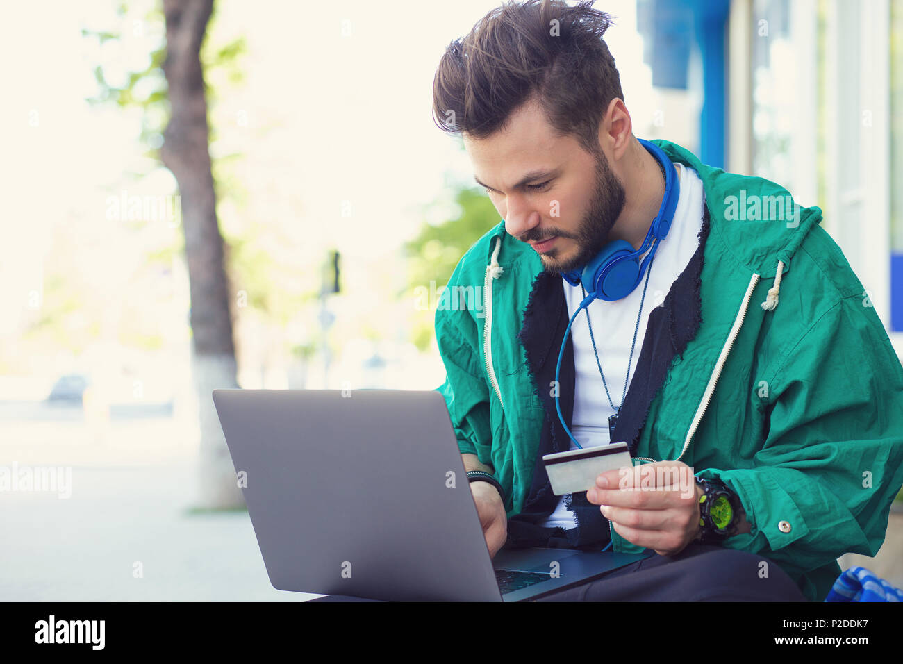 Stylish hipster man sitting on street with laptop on knees and doing online purchase with credit card - Stock Image