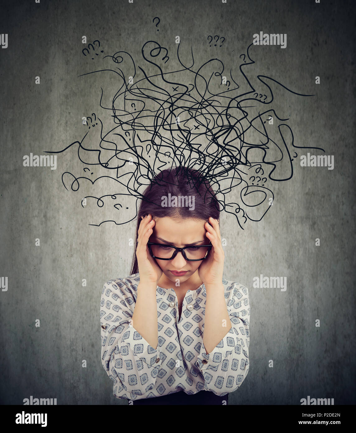 Girl in glasses having problems with mental health and looking deep in chaos on gray background - Stock Image