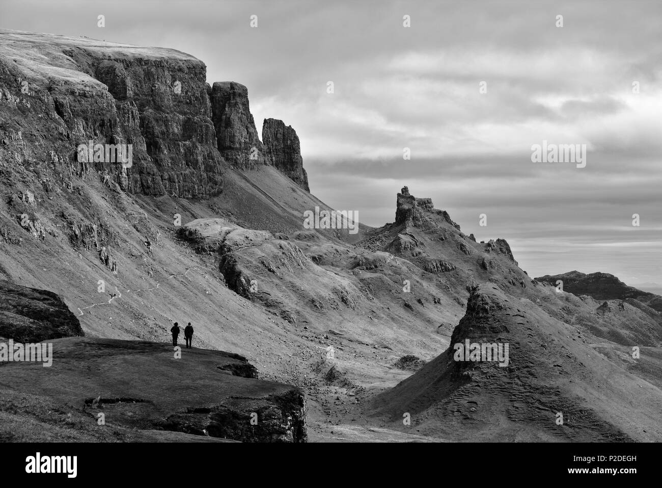 Quiraing, Isle of Skye, Scotland - Bizarre rocky landscape with two human figures standing on a cliff in the foreground - Stock Image