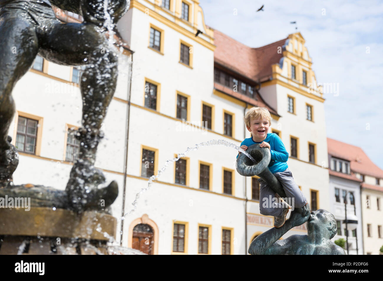 Boy sitting on the fountain outside the town hall, Torgau, Saxony, Germany, Europe Stock Photo