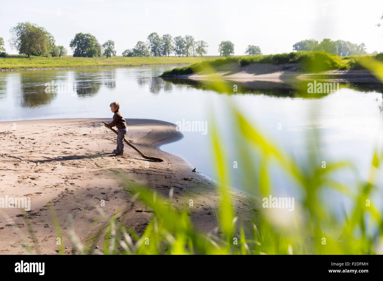 Boy playing near the river, Family bicycle tour along the river Elbe, adventure, from Torgau to Riesa, Saxony, Germany, Europe Stock Photo