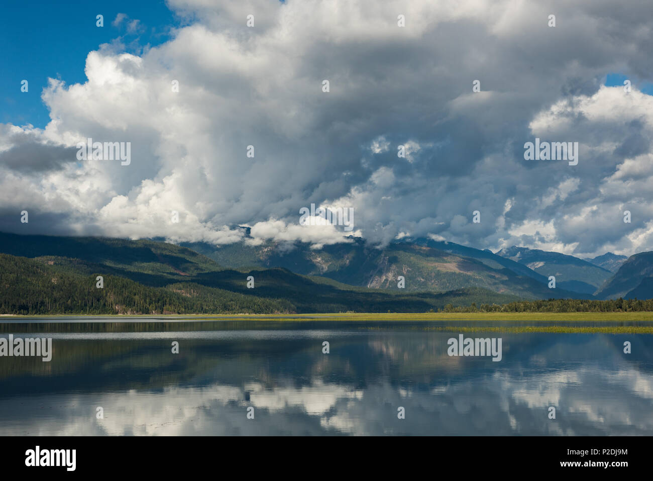 Cloudy sky over green mountains and river - Stock Image