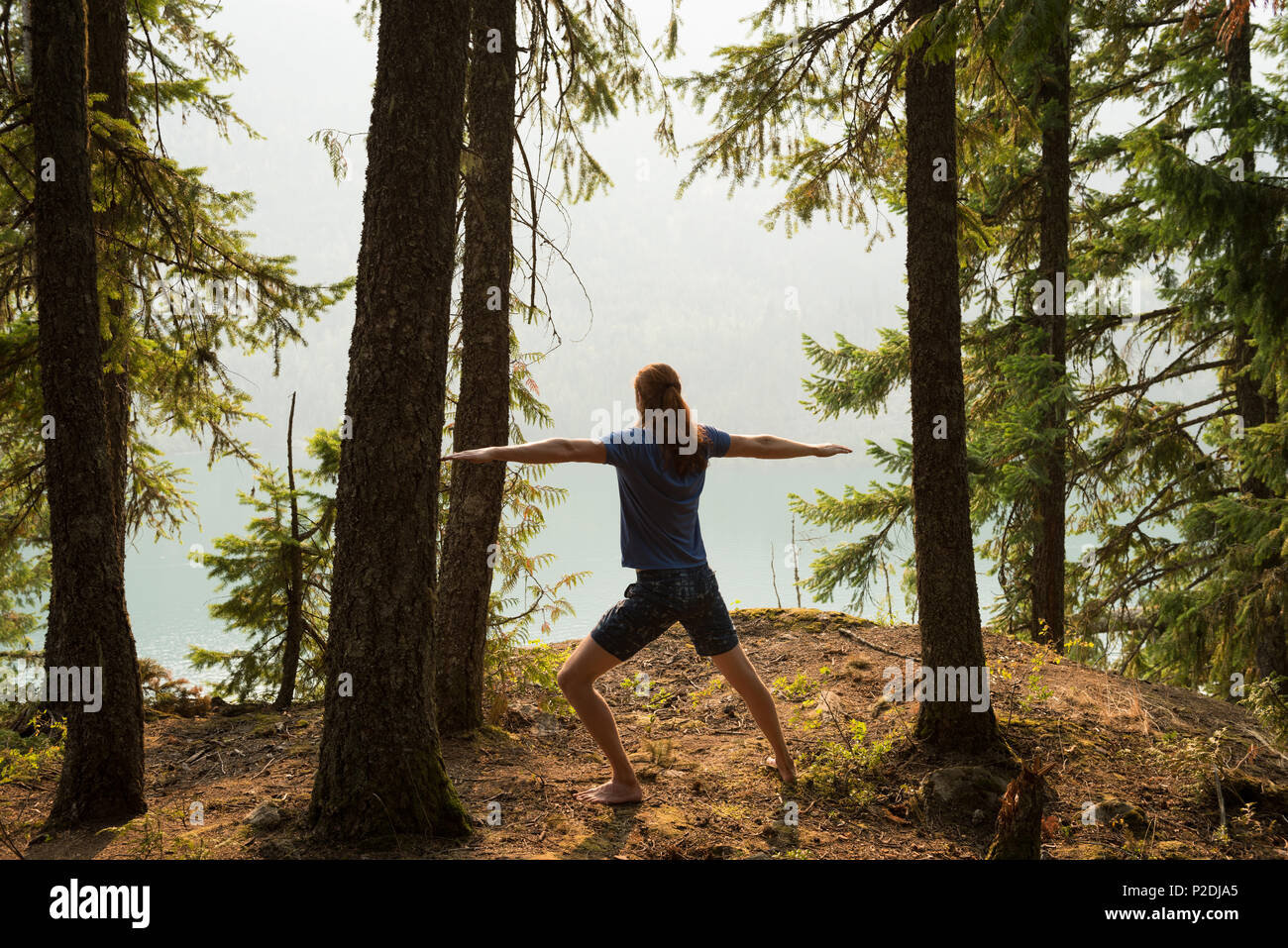 Fit man performing stretching exercise in a lush green forest - Stock Image