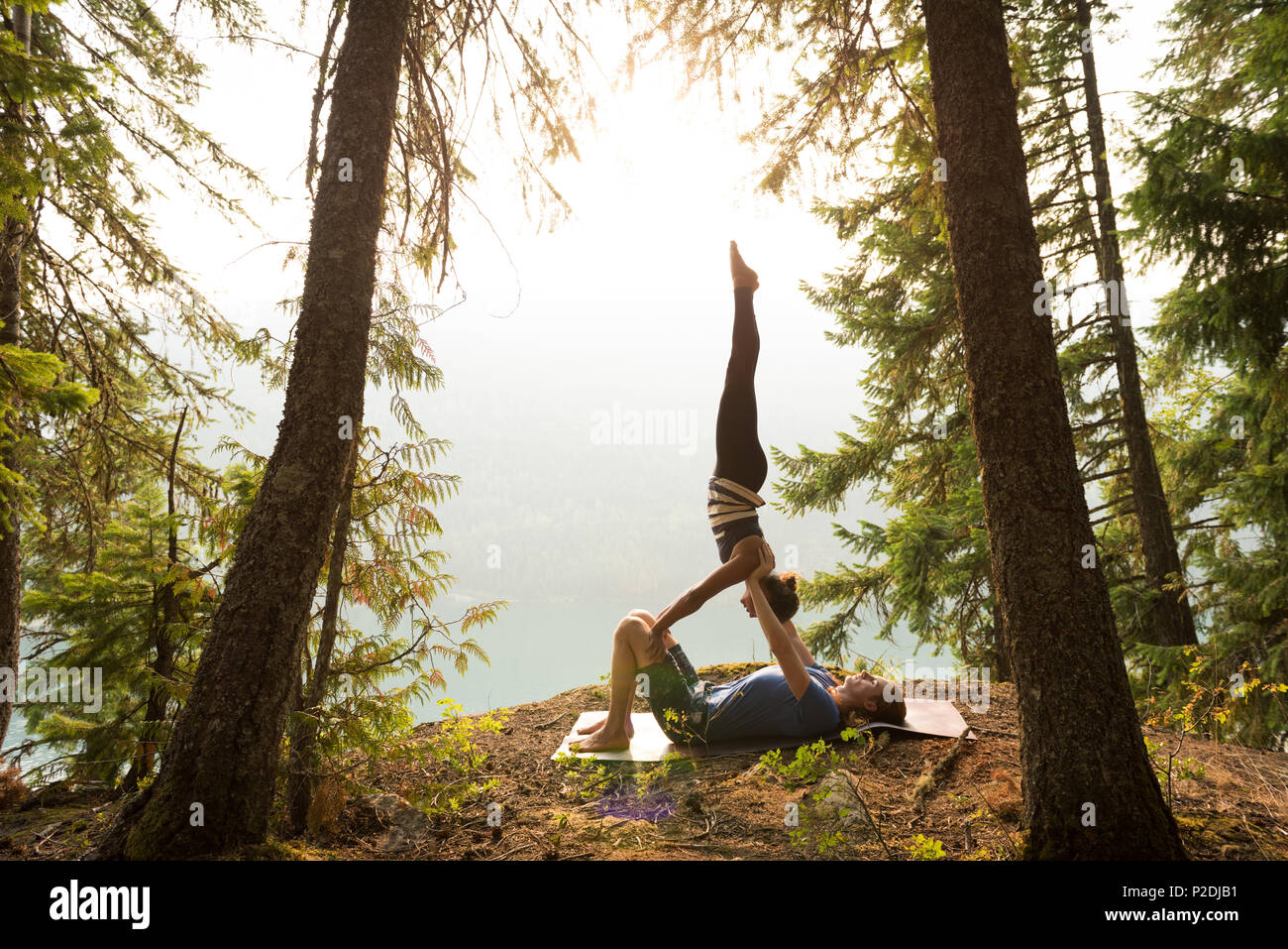 Sporty couple practicing acro yoga in a lush green forest - Stock Image