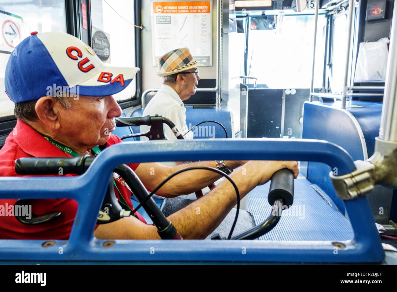 Florida Miami Beach bus Miami-Dade Metrobus public transportation Hispanic senior man walker baseball cap passengers - Stock Image
