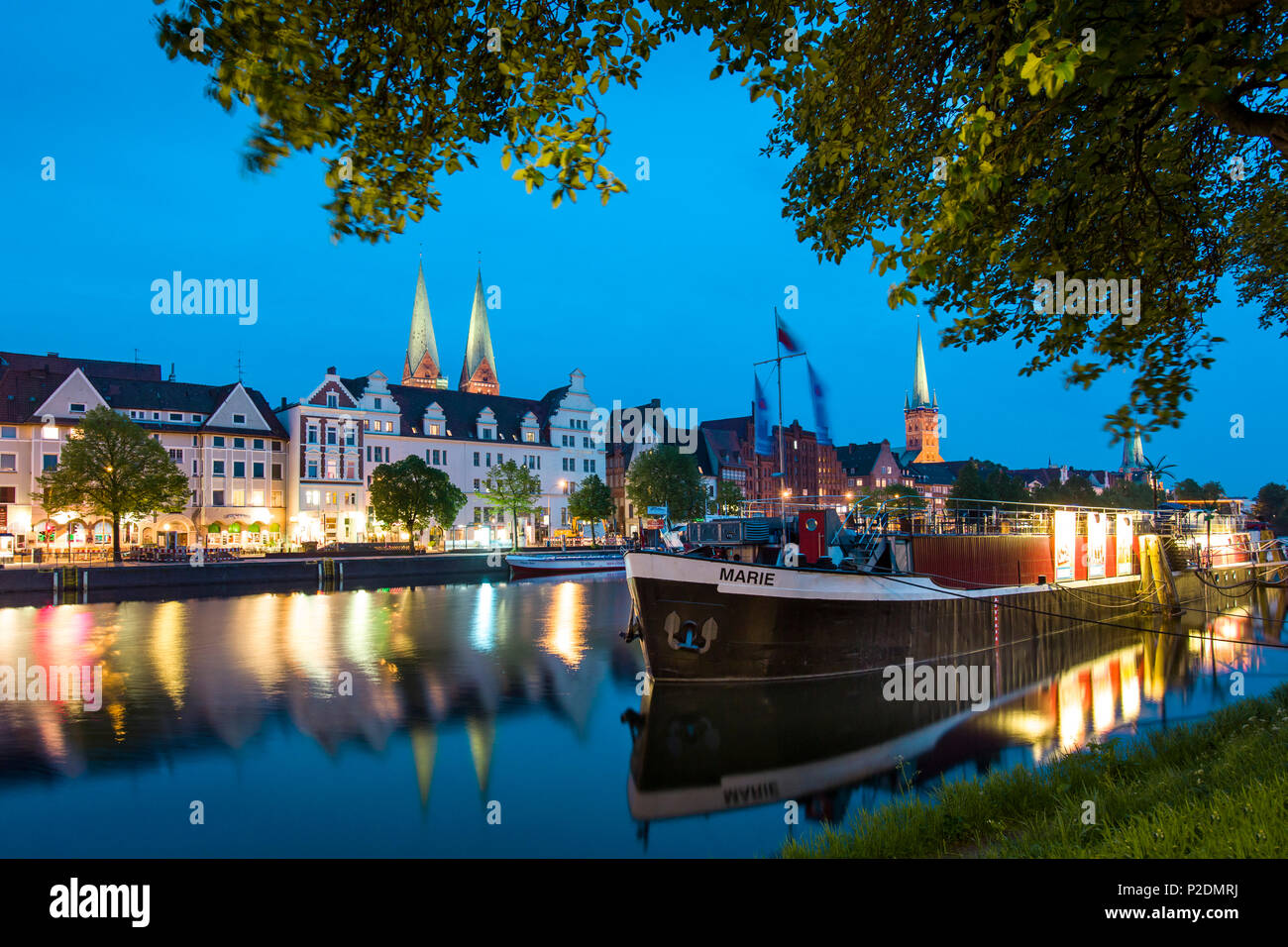 View over river Trave at night towards the old town with the church of St Mary and church of St. Peter, Hanseatic City, Luebeck, - Stock Image