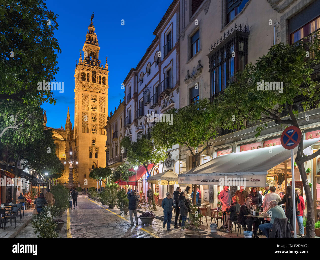 Seville, Spain. Cafes on Calle Mateos Gago at night looking towards the Giralda tower and Cathedral, Barrio Santa Cruz, Sevilla, Andalucia, Spain - Stock Image