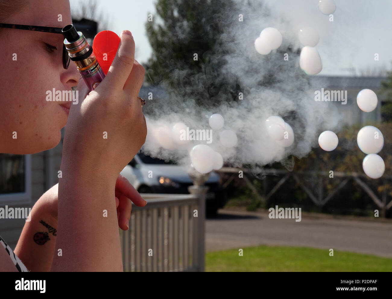 Woman blowing bubbles filling them with smoke from a modern vaping cigarette. - Stock Image