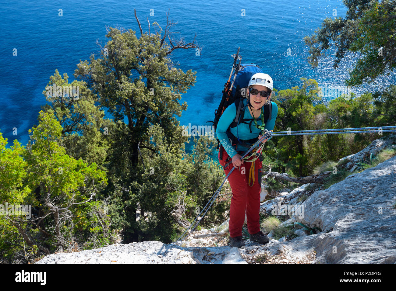 A young woman with trekking gear abseiling in the mountainous coastal landscape above the sea, Golfo di Orosei, Selvaggio Blu, S - Stock Image