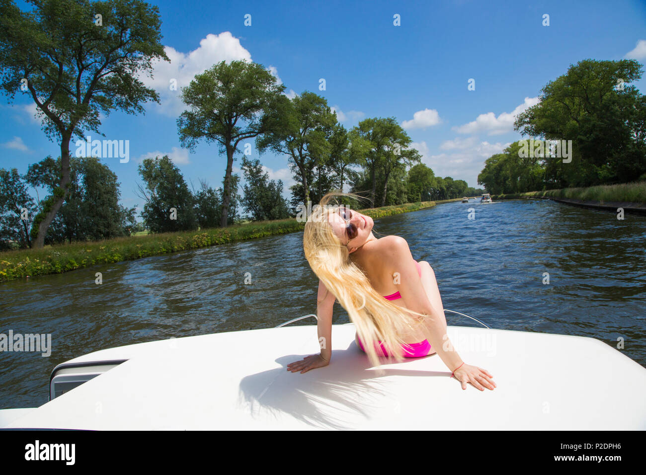 Young blonde woman wearing a bikini relaxing on the deck of a Le Boat Royal Mystique houseboat on Plassendale - Niuewpoort canal Stock Photo