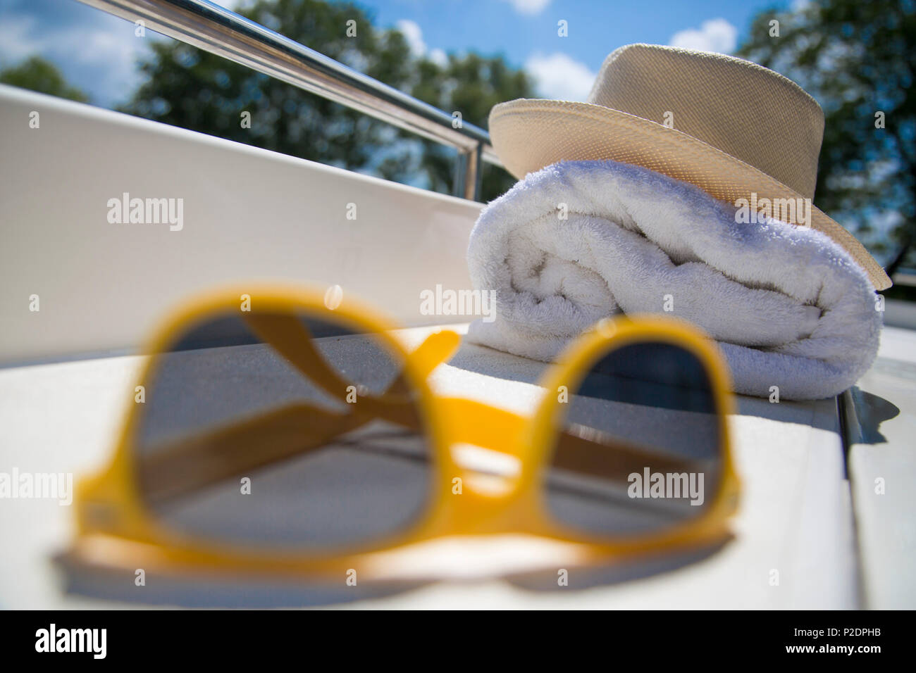 Still life with yellow sunglasses, hat and towel on deck of Le Boat Royal Mystique houseboat on the Bruges - Ostend canal, near - Stock Image